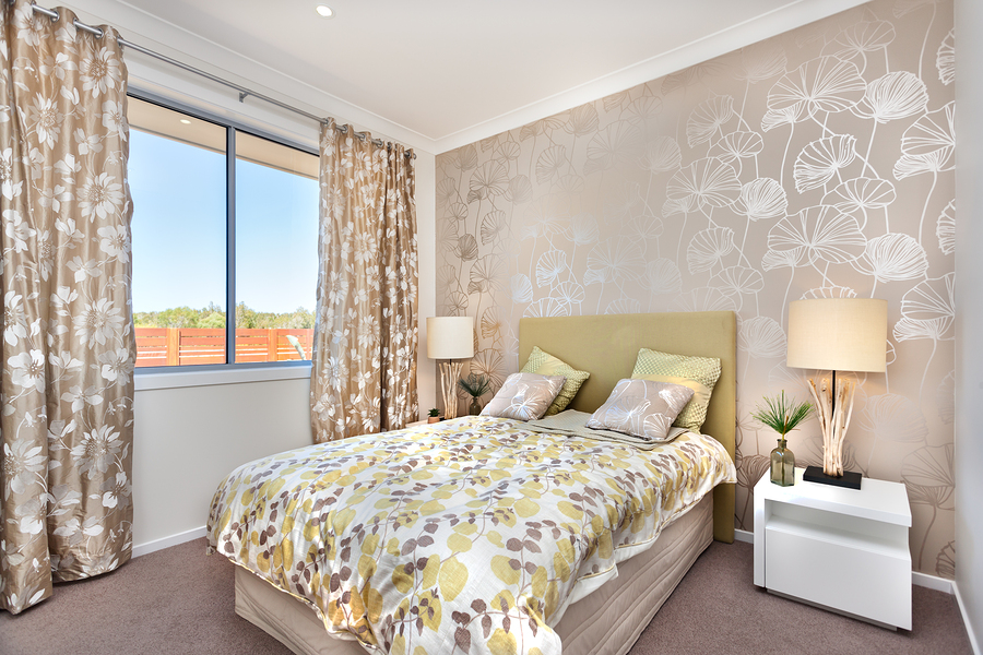 Luxury bed is little bit tall from the carpet floor and it has a light color bed sheet with leaf and vine patterns four gray color pillows and yellow color pillows are on the bed Two table lamps on the cupboards from left and right side which has covered